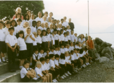 primary students posing for a group photo on the shore of lake geneva
