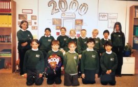 primary students posing for a group photo in the their classroom with 2000 written on the wall behind them