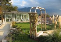 a photo of a wooden archway in the garden at the top of roches grises with mountains in the background