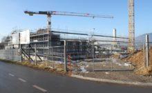 scaffolding surrounding the praz-dagoud campus under construction behind a fence
