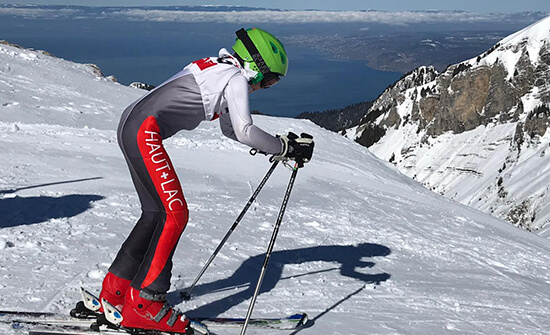 student in a ski suit preparing to start a slalom run while skiing