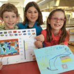 three primary students displaying their work