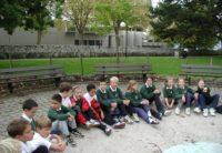 old photo of primary students sitting by a water fountain in vevey