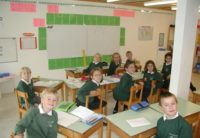 old photo of primary students sitting at their desks smiling for the camera